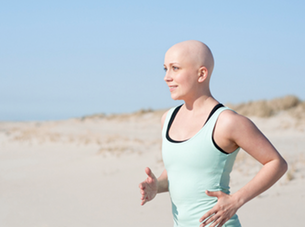 woman on chemotherapy running on the beach