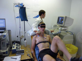 A subject on an exercise cycle ergometer has his blood flow measured.